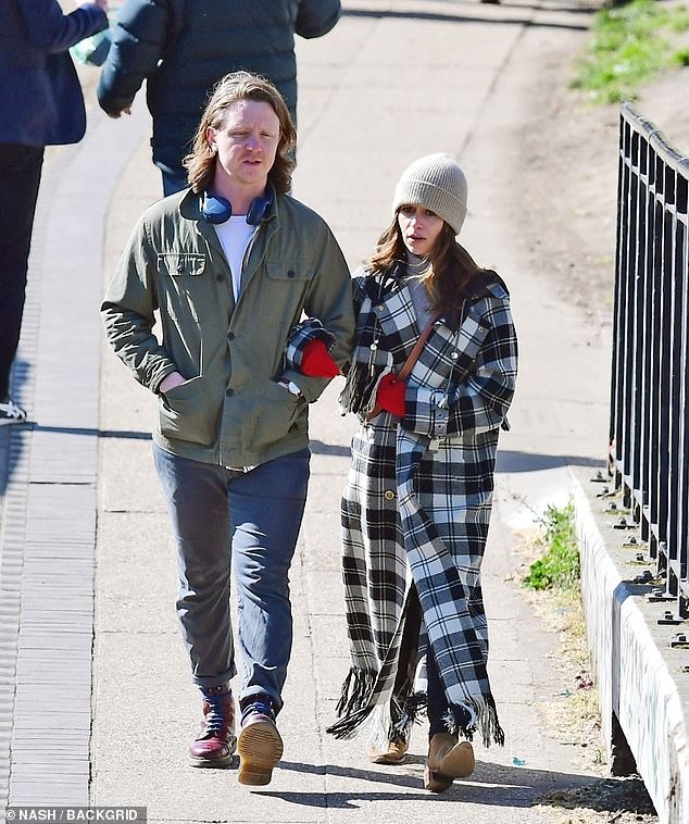 Out: Emilia Clarke was seen arm in arm with a mysterious man as they enjoyed a romantic stroll in London on Thursday
