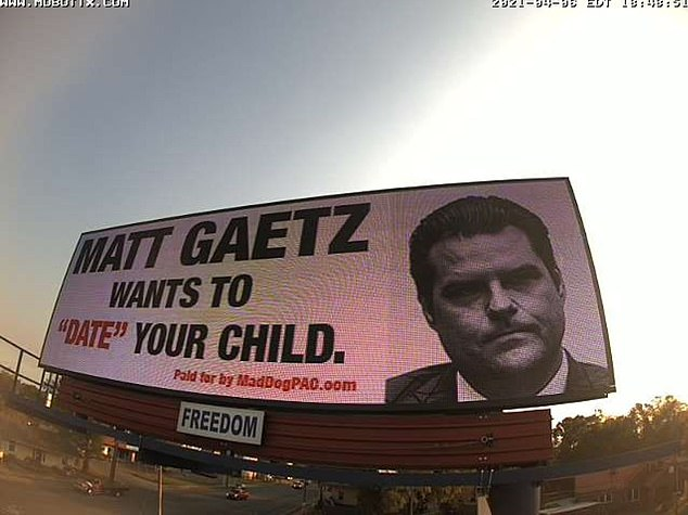 The sign features a black and white photo of the embattled congressman with the striking claim: 'Matt Gaetz wants to 'date' your child.'