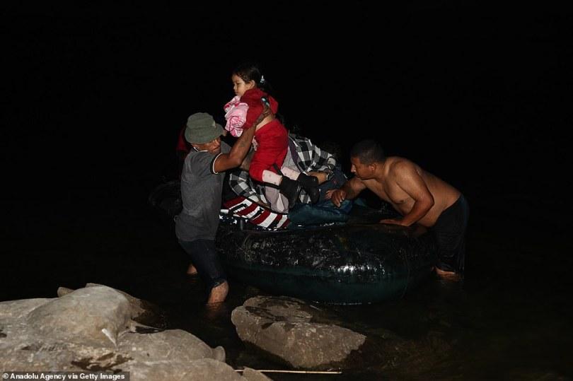 Migrants,departing from Honduras, Guatemala and El Salvador, are seen crossing the Rio Grande River Wednesday night