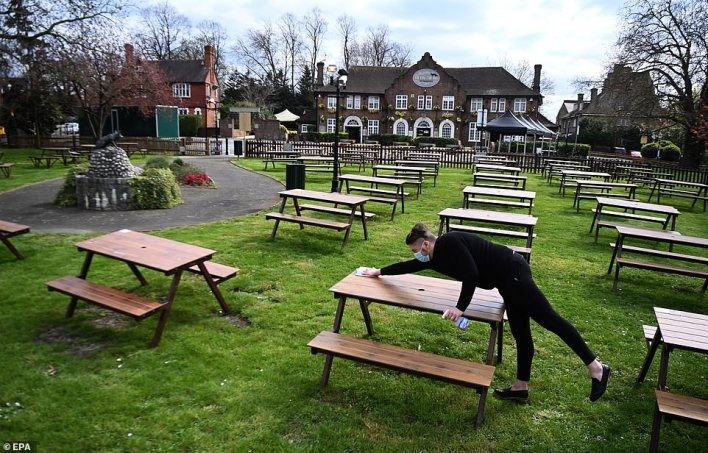 Pub-goers will be able to return to their favourite local for the first time in months from Monday as the country enters its second phase of lockdown easing, with some pubs throwing open their doors at a minute past midnight. Pictured:A staff member wipes down tables at the The Fox on the Hill pub in Camberwell, London
