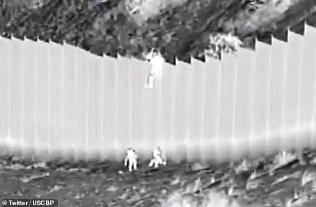 Footage release by U.S. Customs and Border Protection shows a human smuggler (top) climbing over the Mexico-United States border wall in New Mexico after dropping two sisters from Ecuador, aged 3 and 5, over the steel barrier last Tuesday