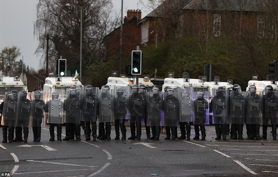 PSNI officers with riot shields line the Springfield road, during further unrest in Belfast on Thursday evening. The cause of the unrest has been attributed to frustration over a decision not to prosecute members of Sinn Fein over alleged coronavirus regulation breaches at the funeral of republican Bobby Storey