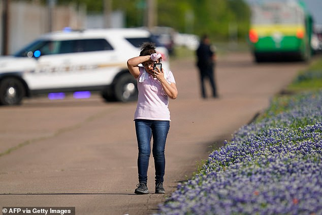 An employee from a local business talks on her phone after police released her from the scene of a mass shooting at an industrial park in Bryan, Texas