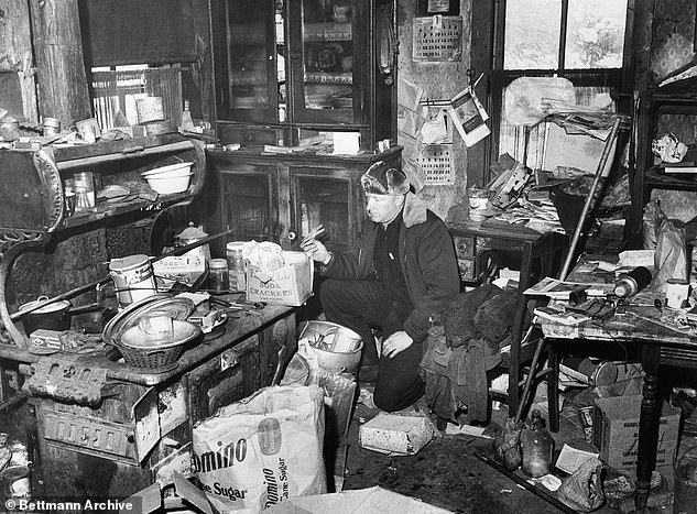 An unidentified police officer examines the junk-littered kitchen in the farm home of Edward Gein, where authorities found human skulls and other parts of human bodies. They also found the butchered body of Bernice Worden hung in a shed near the house