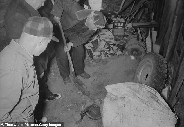 Overhead view of police investigators as they dig for evidence in a garage on the property of murderer and body snatcher Ed Gein in 1957