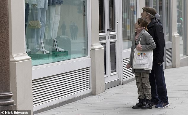 A group of people look at a shop window on Oxford Street yesterday ahead of West End stores reopening next week