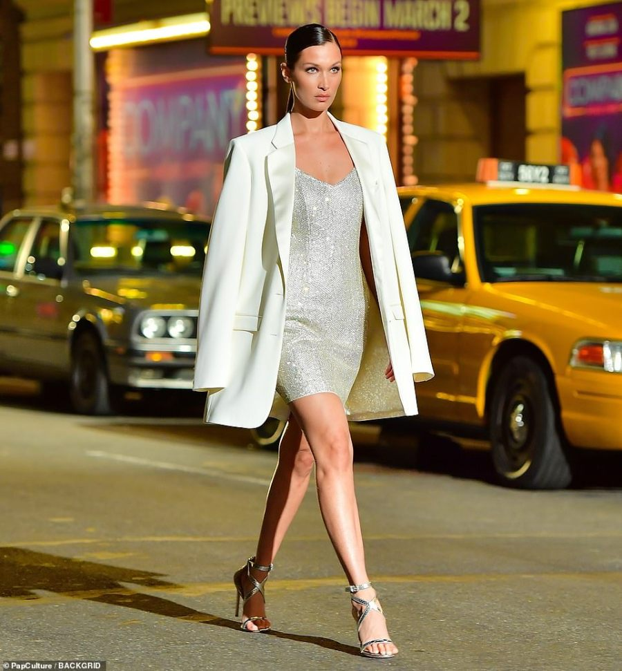 Covered up: She covered up the revealing look a bit and fought back against the cool temperatures with a lustrous white blazer that she wore draped over her shoulders while leaving her arms unencumbered