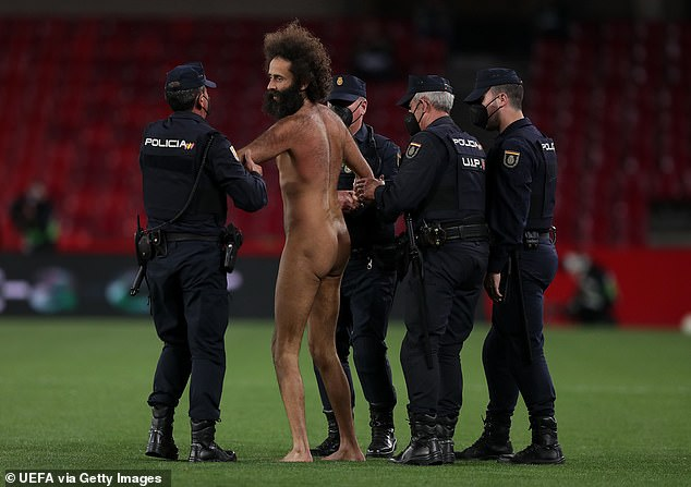 Garcia is led off the field by four police officers after his daring stunt on Thursday evening