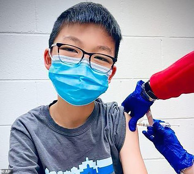 FDA official said approval of COVID-19 vaccines in children under age 12 is expected in early or midwinter. Pictured: Caleb Chung receives the first dose of Pfizer coronavirus vaccine or placebo as a trial participant for kids ages 12 to 15, December 2020