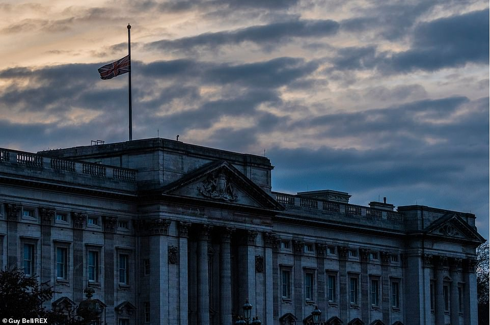 The sun sets behind the flag which is at half mast atBuckingham Palace. Mourners rushed to lay flowers in tribute