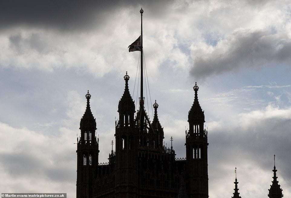 Flags are lowered to half mast following Prince Philip's death. The silhouette of theHouses of Parliament can be seen