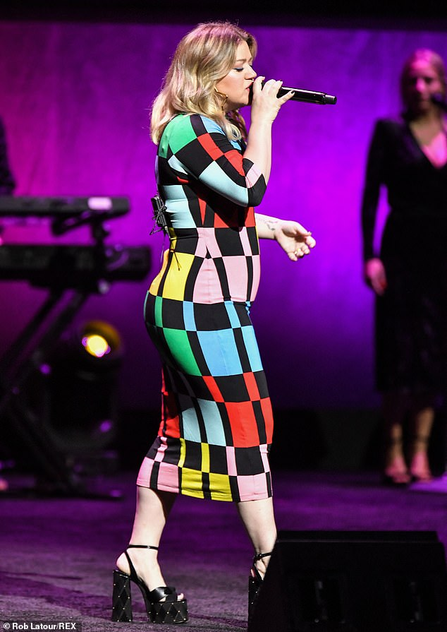 Doing Her Thing: Clarkson is known for her extensive touring schedule and energetic performances, as well as her friendly stage presence;  we see her sing in 2019