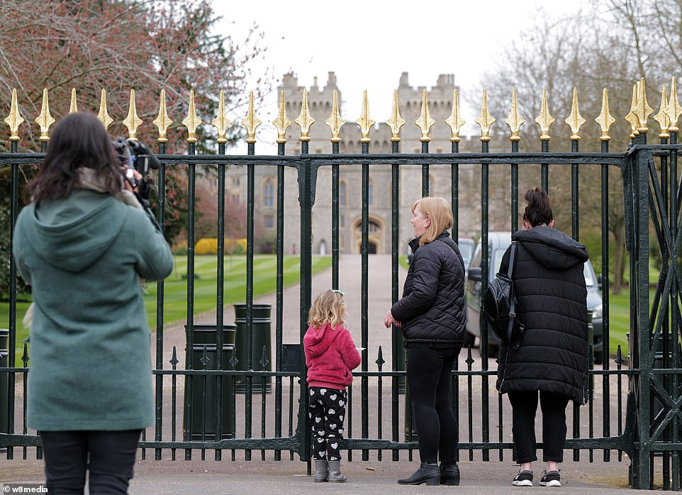 Families gather at the gates of Windsor Castle at the top of the Long Lane, with one woman bowing her head in tribute