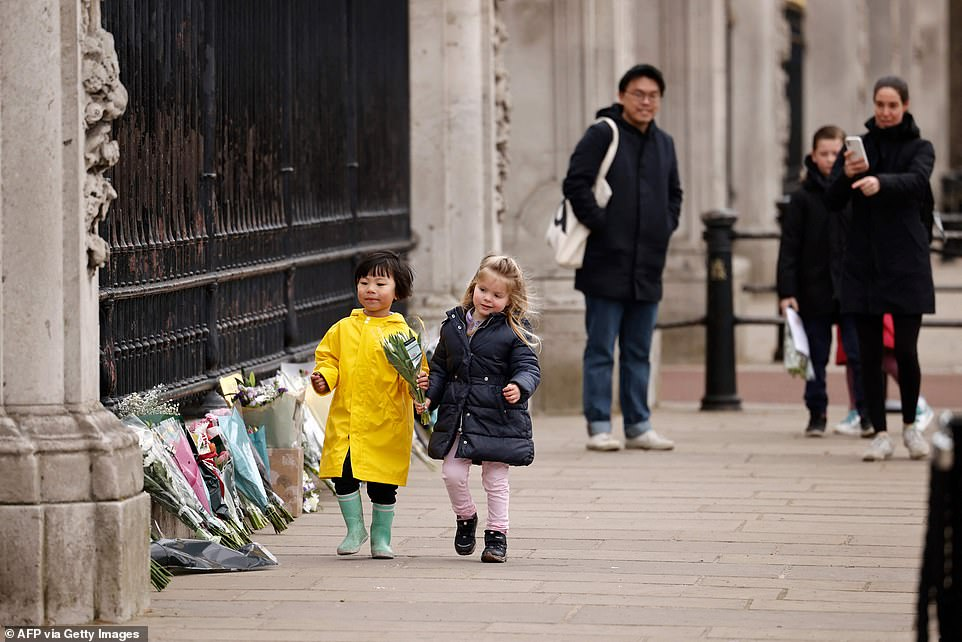 But despite the warnings, still the mourners come, with these children sent by their parents to lay a bouquet together at the palace