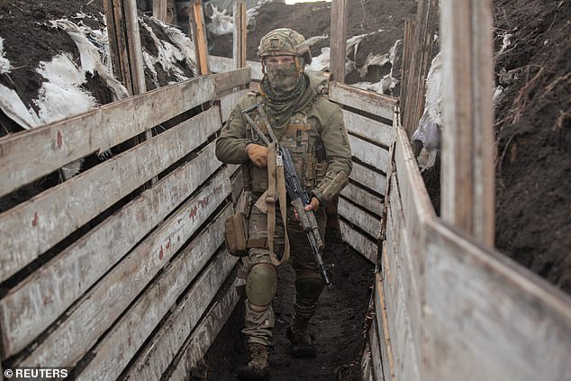 A member of the Ukrainian armed forces walks near the rebel-controlled city of Donetsk, Ukraine