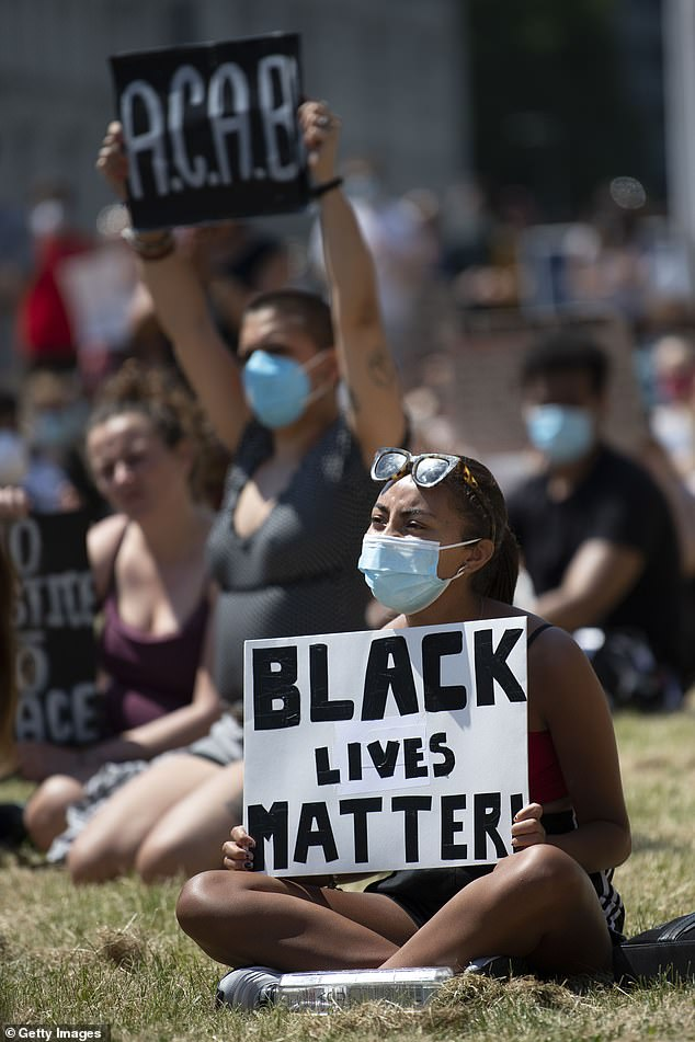 The authors said the BLM movement 'provides a particular context to the conclusion of our work and brings into sharp focus the issues of diversity highlighted throughout our report'. (Pictured, a woman holds a sign saying 'Black Lives Matter' during a protest outside Cardiff Castle in response to the death of George Floyd on May 31, 2020)