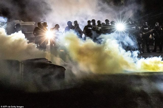 Police officers in riot gear fire tear gas in front of the Brooklyn Center Police Station as people gather to protest after a police officer shot and killed Daunte Wright in Brooklyn Center, Minneapolis, Minnesota