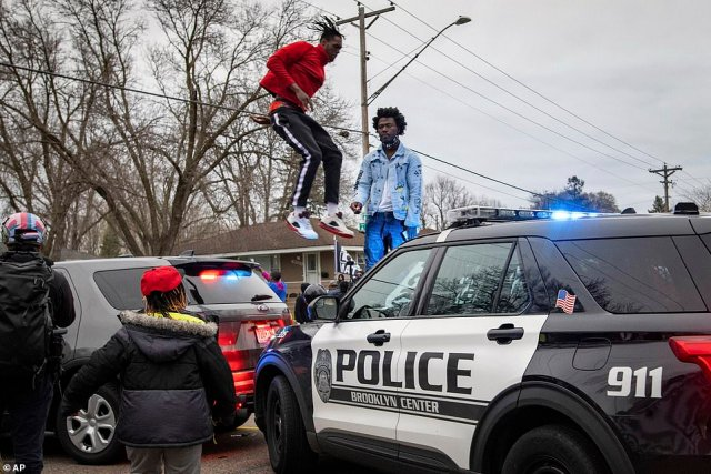 A man can be seen jumping on the hood of a Brooklyn Center patrol car