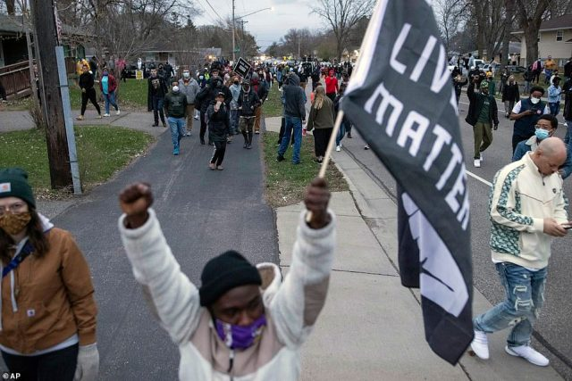 People march in protest Sunday in Brooklyn Center, Minn. The family of Daunte Wright, 20, told a crowd that he was shot by police Sunday before getting back into his car and driving away, then crashing the vehicle several blocks away.