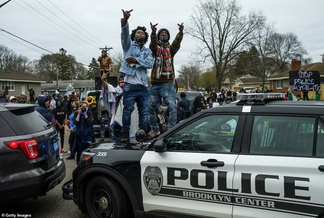 People stand on a police cruiser as protesters take to the streets after a Brooklyn Center police officer shot and killed a black man on Sunday
