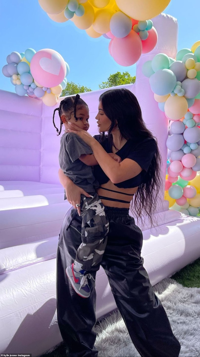 Mommy and daughter:Kylie showcased her midriff in a black crop top with baggy bottoms as she held her daughter Stormi in her arms