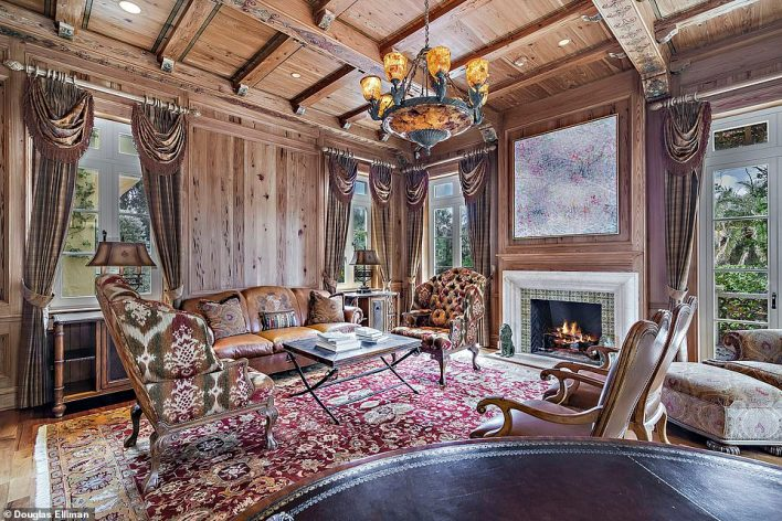 A fireplace can be lit during the cooler months in a room lined with wood