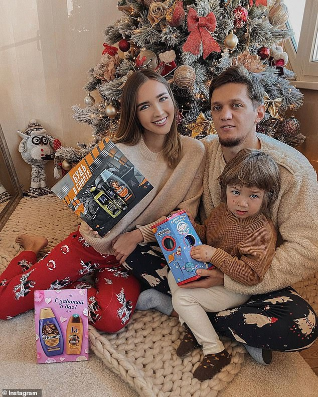 Festive: Ekaterina's image was actually of her and her husband in front of the Christmas tree from a festive photoshoot.Ekaterina is pictured with her husband and their son