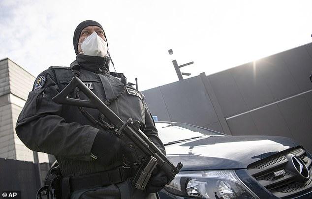 Un policía armado hace guardia frente al juzgado de Stuttgart donde los presuntos terroristas de derecha fueron juzgados hoy.