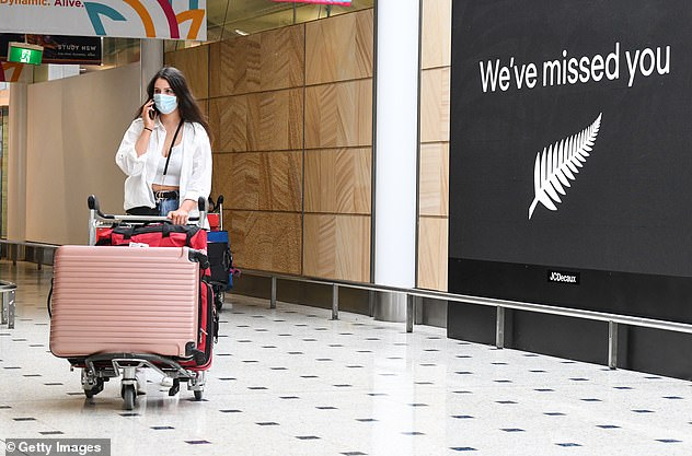 A passenger wearing a face mask arrives at Kingsford Smith Airport in Sydney from New Zealand (pictured) - the only country in the world where Australians can travel