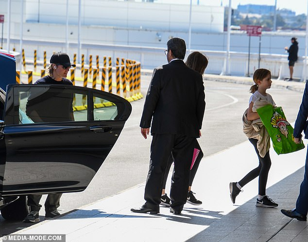 On the move! Cutting a low-key figure, the country singer and his girls were seen arriving at Sydney Airport in a black limousine, before making their way across the tarmac to a private jet