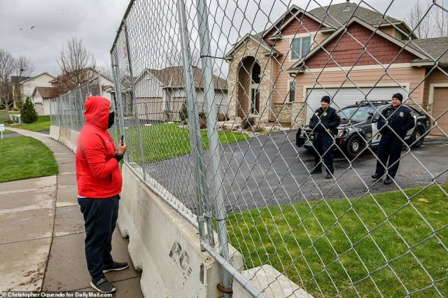 A man speaks with two cops stationed behind barriers and metal fencing put up around the home of Officer Kimberly Potter
