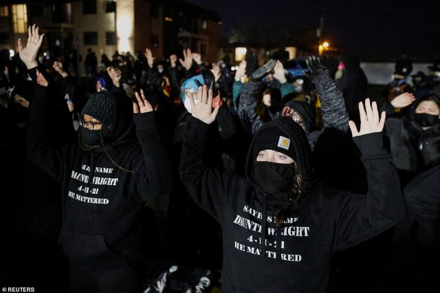 Activists raise their arms as they confront State troopers, National Guard members and other law enforcement officers following a march for Daunte Wright Tuesday.Curfews had been in place for Brooklyn Center, Minneapolis, St. Paul, Crystal, Columbia Heights, New Hope and Maple Grove from 10pm local time before gatherings were declared unlawful