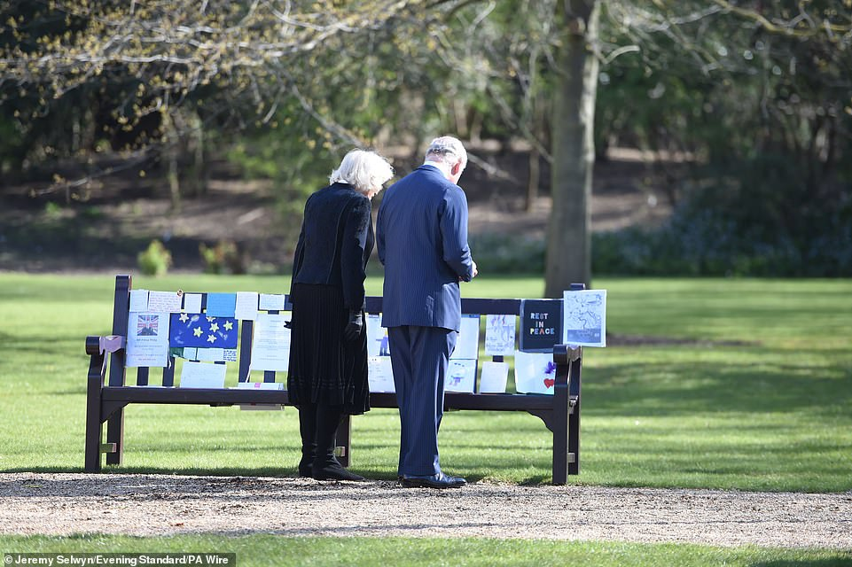 The Prince of Wales and the Duchess of Cornwall look at messages about Philip on a bench at Marlborough House today