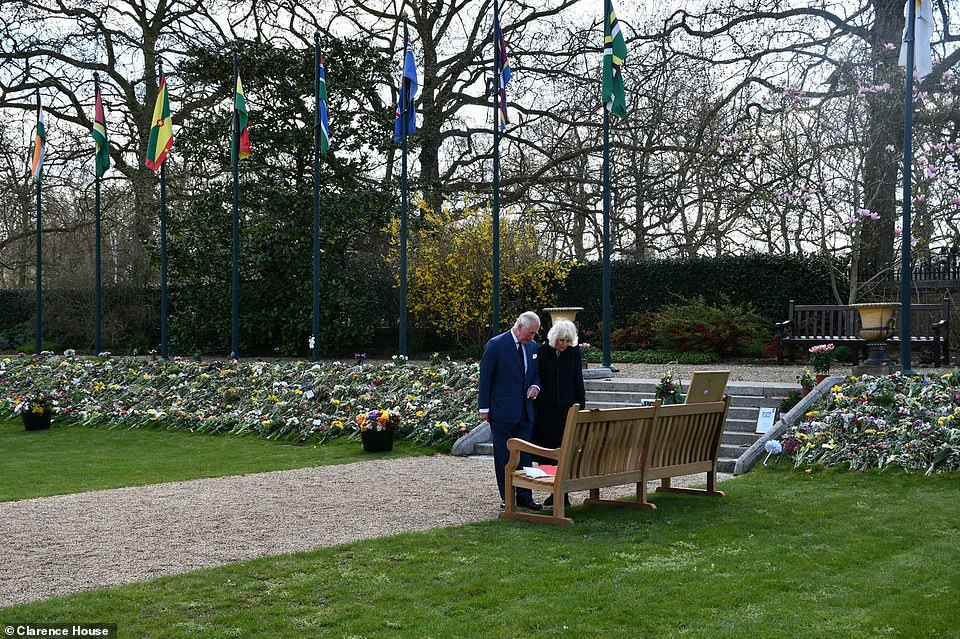 The Prince of Wales and Duchess of Cornwall view a selection of flowers today that have been left by members of the public