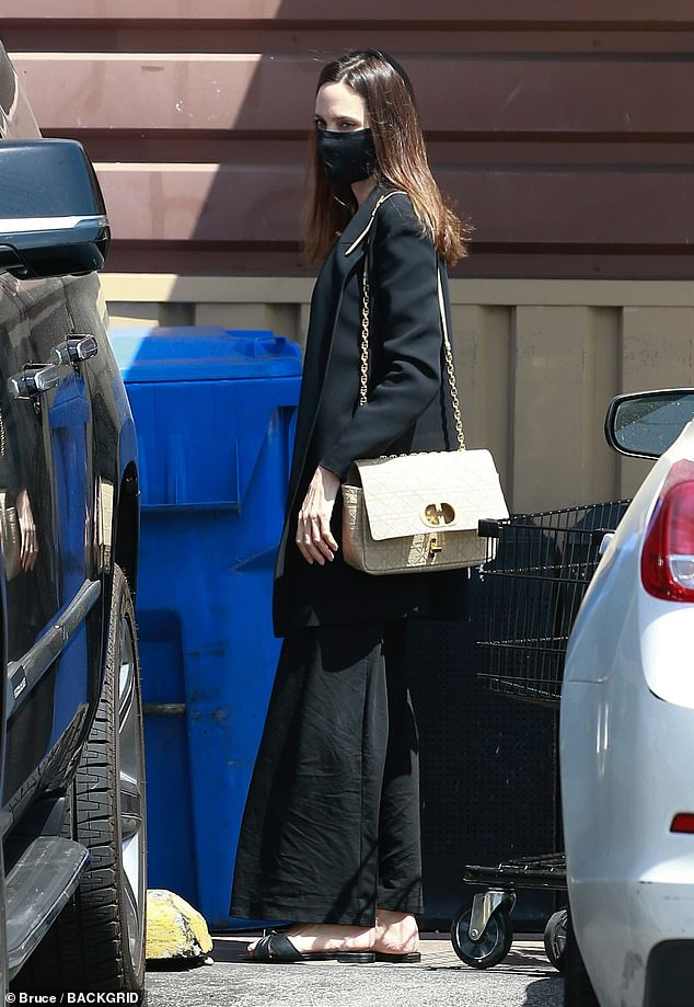 Chic: Jolie looked undeniably chic in an oversized black blazer that she layered over a black, sleeveless maxi dress