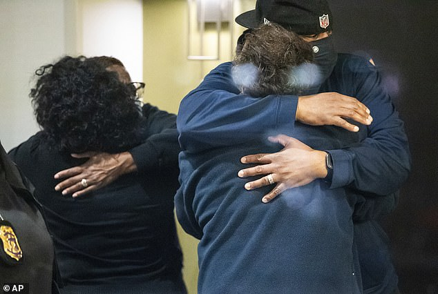 Pictured:People hug after learning that their loved one is safe after a shooting inside a FedEx building Friday, April 16, 2021