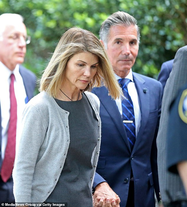 They're both free: Lori Loughlin's husband Mossimo Giannulli is officially finished with his scheduled home confinement a day ahead of time, TMZ reported on Friday (The couple pictured at a federal courthouse in 2019)
