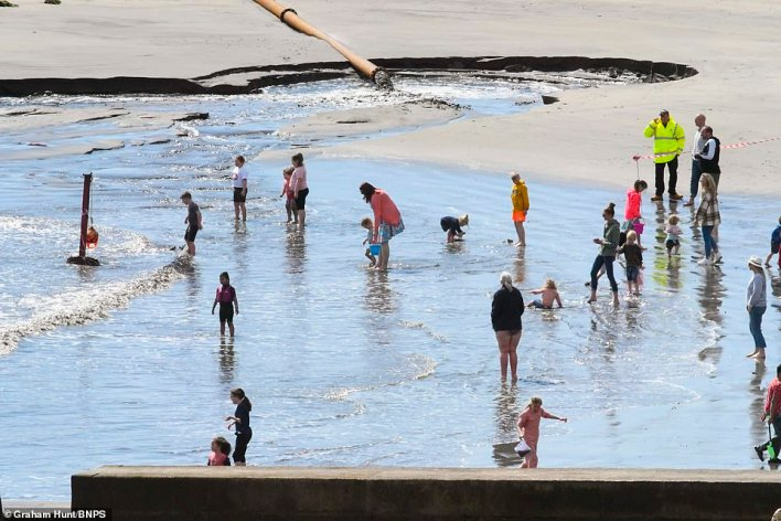 Families go for a paddle at Lyme Regis in Dorset this afternoon as they make the most of the pleasant weather
