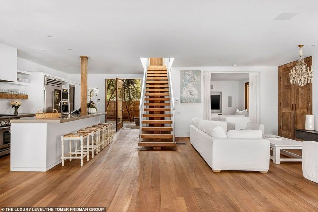 An open air feel that is calming: The wood floor kitchen has a large island that looks out to the living room space and is also connected to a yard with olive trees