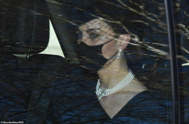 The mother-of-three wore an elegant pearl necklace, black face covering and black hat with lace mesh covering her eyes