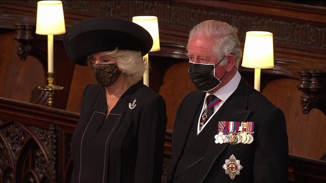 A tearful Prince Charles watches as his father's body is carried to the altar, as he is supported by his wife Camilla