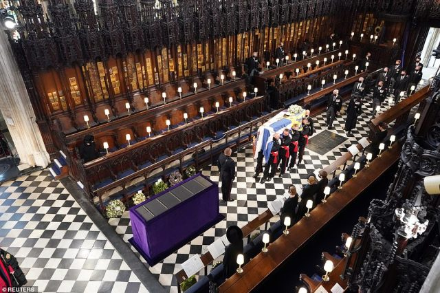 The Queen sits alone as pallbearers carry the coffin of her husband of 73 years Prince Philip into St George's Chapel