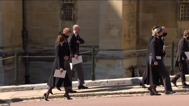 Prince Harry and Prince William walk together out of St George's Chapel today as Kate Middleton also walks alongside them
