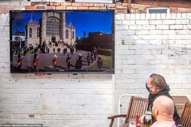 Drinkers at the White Bull pub in Chorley, Lancashire, watch the funeral of the Duke of Edinburgh on a television in the beer garden