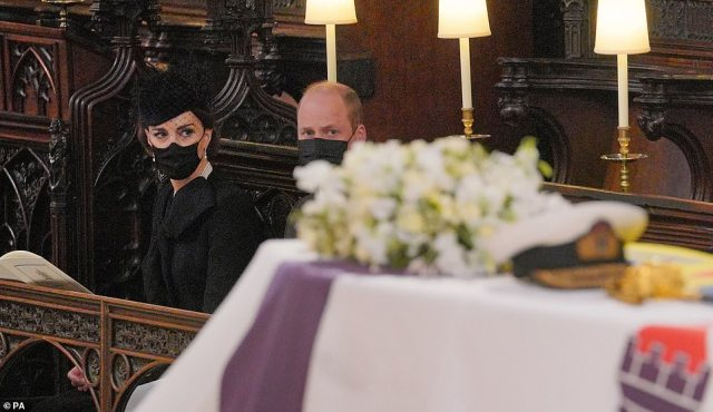 The Duchess of Cambridge and the Duke of Cambridge look towards Philip's coffin before it was lowered into the Royal Vault
