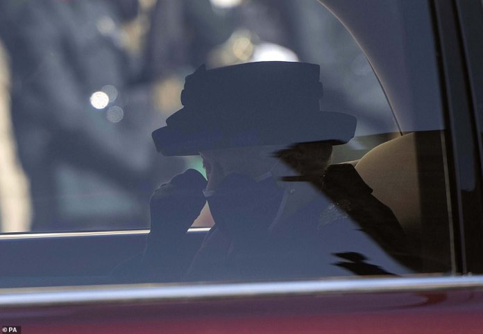 The emotional Queen wipes a tear from the back of the Royal Bentley as she sees the procession carrying Prince Philip's coffin