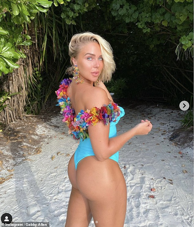 Gorgeous: Sharing another snap from her stay at Kandima Maldives, Gabby slipped into a bright blue Truffle Bikinis one-piece styled with some pretty flowers around her back