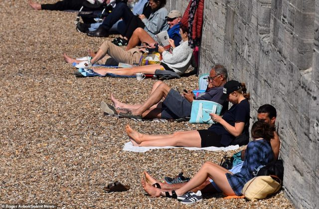 Temperatures continued to rise today, with a mini-heatwave predicted before it cools off at the end of the week. Pictured: Sun-seekers this morning by the Hot Walls in Portsmouth