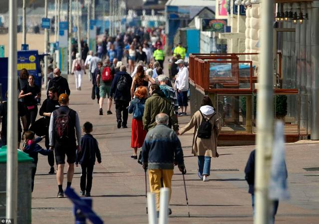 People walk along the seafront in Bournemouth today as lockdown-weary Brits begin to enjoy the easing of restrictions