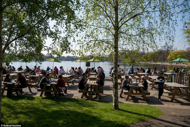 Groups of people sit on outdoor tables placed out at Hyde Park in London today as the country enjoyed a mini heatwave